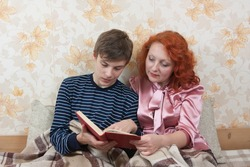 Mother helping son to study homework on sofa