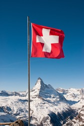 A mountaintop view of the national flag of Switzerland with the Matterhorn in the background