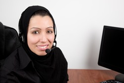 Arabic beautiful young woman with headphones with microphone in the office