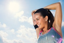 Close up face shot of attractive  young runner getting ready for morning run.Woman with charming smile stretching arms and neck against sunny sky.