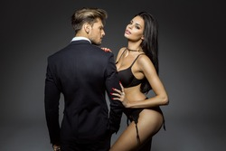 dark haired woman in black lingerie leans on the shoulder of a man in a suit