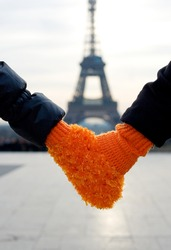 Romantic couple in Paris. Male and female hands in a single glove for two
