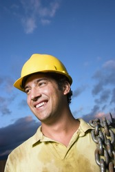 Attractive Caucasian construction worker in a yellow hardhat carries a heavy chain over his shoulder while smiling to the side. Vertical shot.