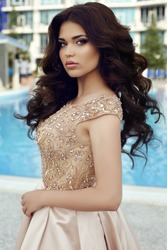 beautiful brunette woman in a gold dress stands in front of a pool