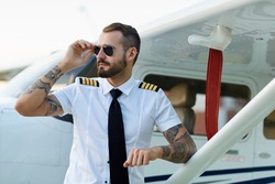 Cool young adult pilot with tattoos in sunglasses posing at private motor airplane on runway near hangar.