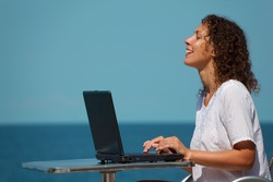 Laughing girl with laptop. Sits at table on beach, warm sunny day.