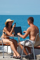 Man and woman sitting at table under open sky on background of sea. Man works for laptop. Vertical format.