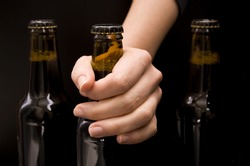 Close-up of a female hand holding a bottle beer isolated on black
