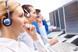 Image of customer service team in headsets working with businesswoman in front