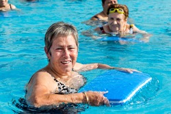 Close up portrait of senior woman doing water exercise with kicking board in outdoor pool.