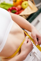 Thin and beautiful woman (only torso) measuring her waist with a tape measure, in the background fruit in a bowl