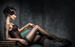 dark haired slim woman seductively lying on a gold and blue sofa