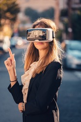 Geeky young beautiful girl gesture testing virtual reality 3D video glasses VR headset dressed in a office outfit gesture in the air with the hand touching augmented reality environment