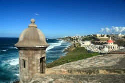 Sentry box overlooking the Atlantic Ocean at 'El Morro' (Castillo San Felipe del Morro) and the La Perla district of Old San Juan, Puerto Rico, including an old cemetery