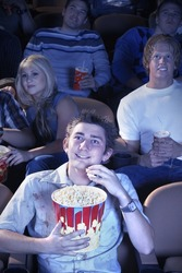 Smiling Man Eating Popcorn, watching movie in Theatre