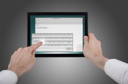 a male hand holding a touchpad pc, one finger touches the screen and writes an e-mail