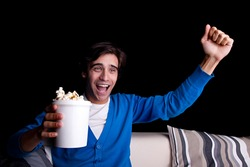 happy young man, with popcorn watching, on black background. Studio shot