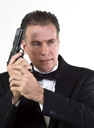 A man in formal attire holding an automatic pistol taken against a white background.