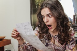 Woman shocked and surprised with her electricity bills
