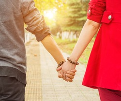oung couple in love walking in the autumn park holding hands loo