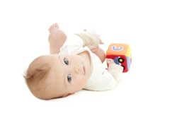 Baby boy rolling on the floor and playing with a colorful block, on white background