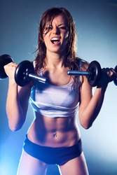 Young strong sexy woman with dumbbells.