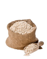 Burlap sack  and scoop of rolled porridge oats isolated on white background