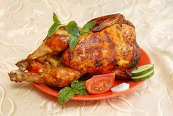 whole grilled chicken served on red plate decorated with vegetables and mint