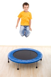 Boy jumping high on trampoline in the gym - isolated, slight motion blur