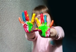 Cute little girl with painted hands.