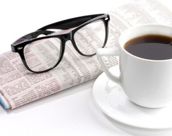 a cup of coffee and newspaper with glasses