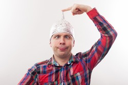 young man in a tin foil hat poses funny faces. Afraid of radiation or aliens