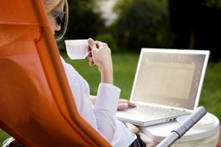 young woman working outside on computer and drinking coffee