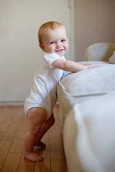 Baby standing up next to furniture