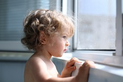 Serious child attentively looks out of the window - shallow depth of field