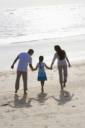 Rear view of Hispanic family with 9 year old girl holding hands walking on beach