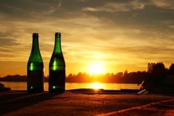 These are two bottles of champagne with sunset in background.
