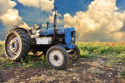 Very old tractor in field, different parts - no trademark at all