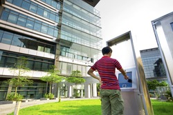 asia boy play the touch screen in modern building outside