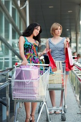 Two young women with shopping carts.