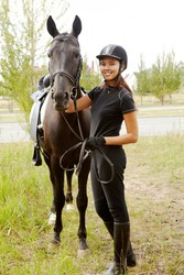 Image of happy female jockey with purebred horse outdoors