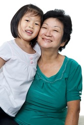 Photo of Asian grandmother and granddaughter on white background.