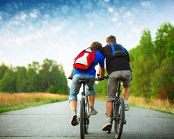 Two riders with backpacks on bikes riding on an rural asphalt roar