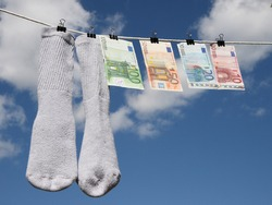 Money laundering. Euros drying up on the rope with the socks.