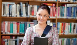 Joyful young caucasian woman holding a book in a book store