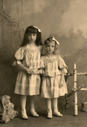 Two little sisters are looking at camera with identical frocks, hair bows and shoes.