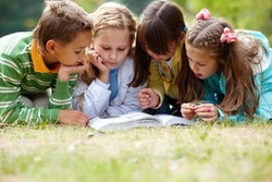 Portrait of cute kids reading book in natural environment together