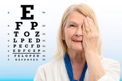Close up portrait of senior woman testing vision with test chart in background.Woman closing one eye with hand.