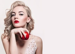 blonde lady holds a red apple