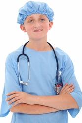 Adorable 12 year old boy dressed in surgical scrubs over white background.